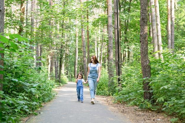 Koncepcja natura, macierzyństwo i dziecko - szczęśliwa matka i córeczka bawią się w zielonym parku.