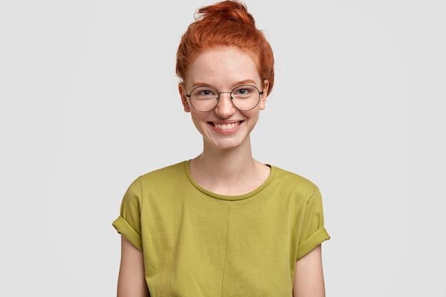 Koncepcja naturalnego piękna i emocji. beztroska, radosna piegowata dziewczyna z delikatnym uśmiechem, zadowolona z pomyślnego zdania egzaminu, nosi casualową koszulkę i okulary, modelki na białej ścianie, ma lśniące włosy