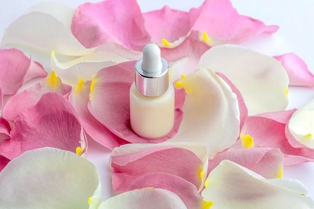 Koncepcja naturalnych organicznych kosmetyków domowych. pielęgnacja skóry, kosmetyki: pojemniki z serum do twarzy wśród delikatnych płatków kwiatów róży.