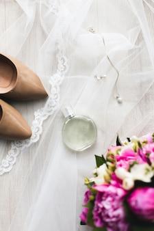 Koncepcja naturalnych perfum. butelka perfum z różowymi kwiatami i dodatkami ślubnymi, biżuteria