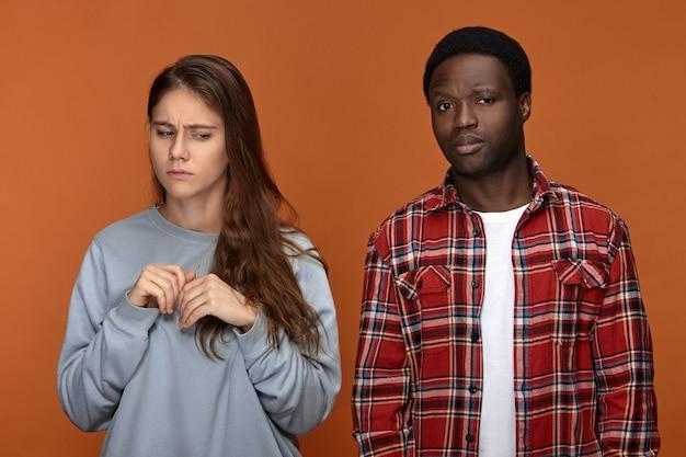 Koncepcja negatywnych ludzkich emocji i relacji. zdenerwowana, niedbale ubrana młoda biała kobieta stojąca w zamkniętej pozycji, zmartwiona, przestraszona ciemnoskórym mężem, sprawcą przemocy