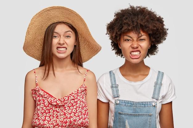 Koncepcja negatywnych mimiki. zirytowane międzyrasowe dziewczyny zaciskają zęby i marszczą brwi z irytacją