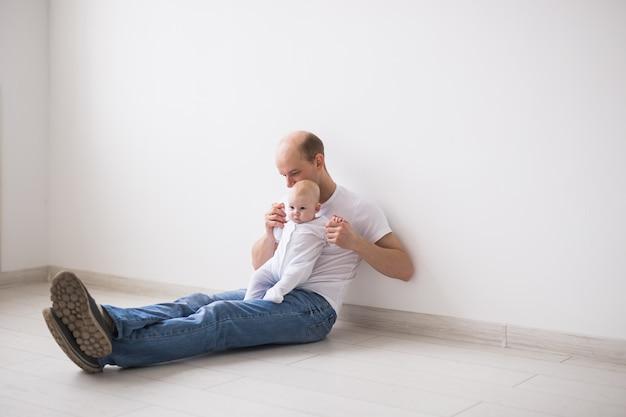 Koncepcja niemowlęcia, rodziny i ojcostwa - łysy ojciec siedzi na podłodze i trzyma swoje małe dziecko