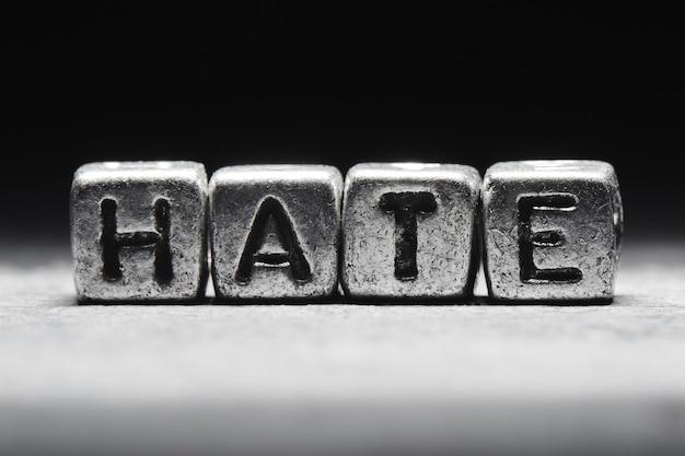 Koncepcja nienawiści. 3d napis na metalowych kostkach na szarym tle czarnym na białym tle w stylu grunge