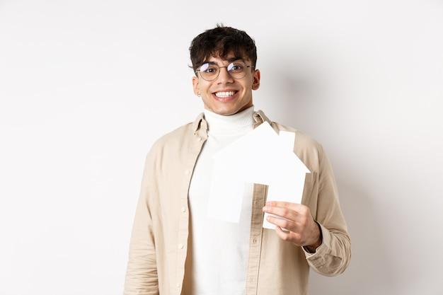 Koncepcja nieruchomości i kredytów hipotecznych. wesoły młody chłopak wynajmujący mieszkanie, pokazujący wycinek papierowego domu i uśmiechnięty szczęśliwy, kupujący nieruchomość, biała ściana.
