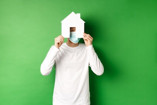Koncepcja nieruchomości i pandemii covid-19. zabawny młody człowiek w masce i biały długi rękaw ukrywa twarz za wycinanką domu papieru, zerkając na aparat, zielone tło.