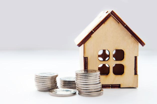 Koncepcja nieruchomości inwestycyjnej. koncepcja kredytu hipotecznego dla domu pieniądze z monet. dom model pieniądze