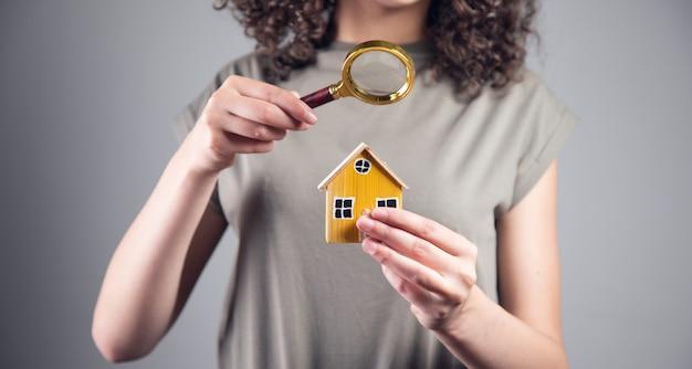 Koncepcja nieruchomości, kobieta trzyma model domu i lupę