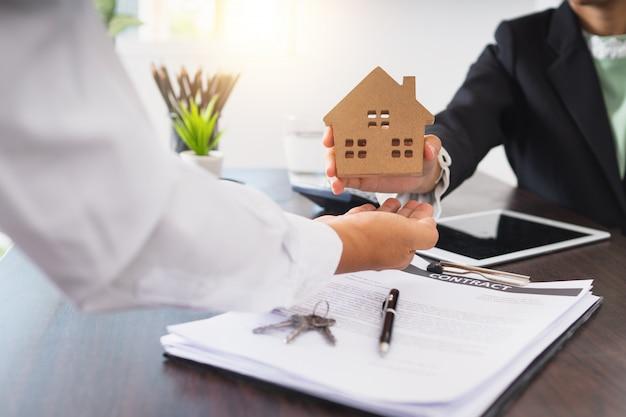 Koncepcja nieruchomości, makler dom mieszkalny daje model domu klientowi