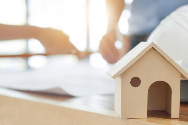 Koncepcja nieruchomości, obraz zabawki drewniany dom nad niewyraźne enginering pracy tle