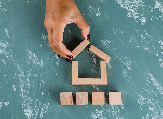 Koncepcja nieruchomości z drewnianymi klockami leżącymi płasko. kobieta co model domu.