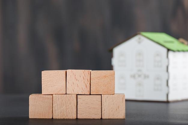 Koncepcja nieruchomości z drewnianymi kostkami, modelem domu i szarością.