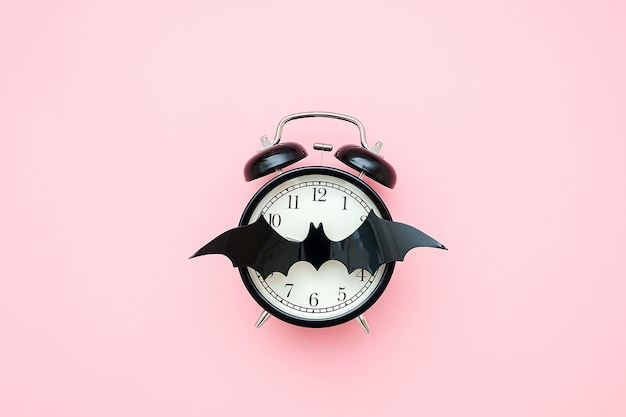Koncepcja nocy halloween. czarny budzik i nietoperz na tarczy zegara na różowym tle. kreatywne mieszkanie leżało