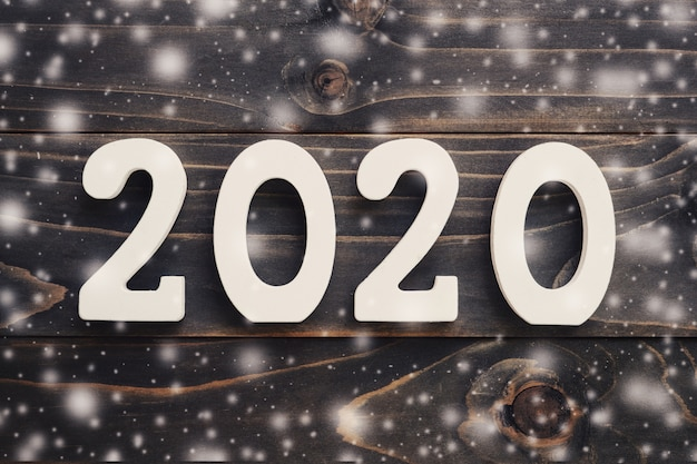 Koncepcja nowego roku 2020: 2020 numer drewna ze śniegiem na tle tabeli.