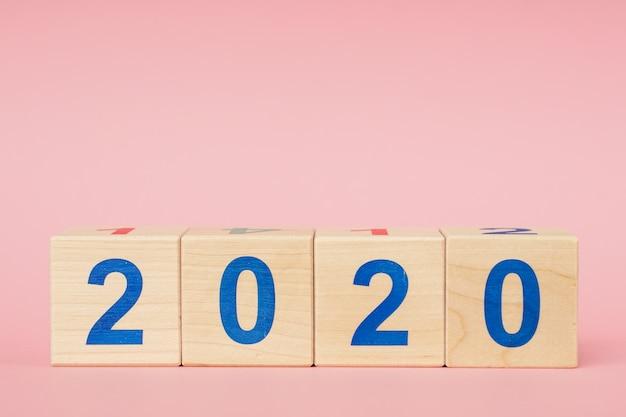 Koncepcja nowego roku 2020. drewniany blokowy sześcian z liczbą na różowym stole
