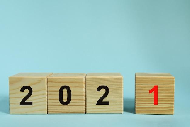 Koncepcja nowego roku 2021, drewniane kostki z numerem na niebieskim tle. makieta do projektowania