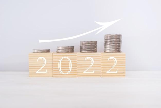 Koncepcja nowego roku 2022. drewniane klocki z tekstem 2022, monetami i strzałką w górę. koncepcja wzrostu finansowego.