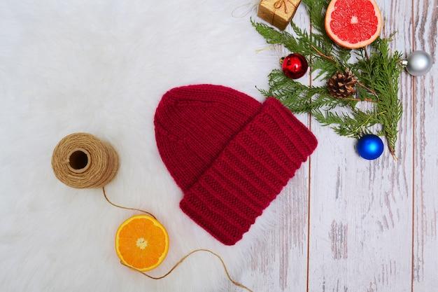 Koncepcja nowego roku. burgundowa czapka zimowa, pomarańczowe ozdoby choinkowe. białe tło