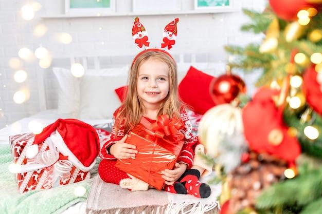 Koncepcja nowego roku i bożego narodzenia, dziewczynka na łóżku w domu z prezentami czekająca na nowy rok lub boże narodzenie w czerwonym swetrze i uśmiechnięta ze szczęścia