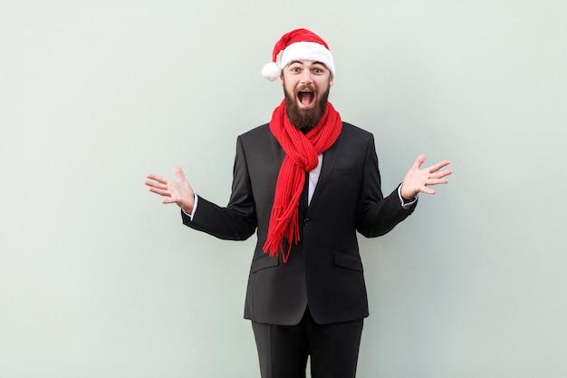 Koncepcja nowego roku. portret biznesmena na nowy rok kapelusz, z szoku wyraz twarzy. patrząc na aparat z otwartymi ustami i dużymi oczami. łapka, na białym tle na szarym tle.