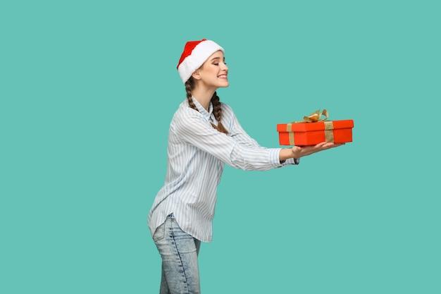 Koncepcja nowego roku. profil widok z boku pięknej dziewczyny w jasnoniebieskiej koszuli w paski w czerwonej czapce świątecznej stojąc i dając czerwone pudełko z uśmiechem toothy. kryty, na białym tle na zielonym tle.