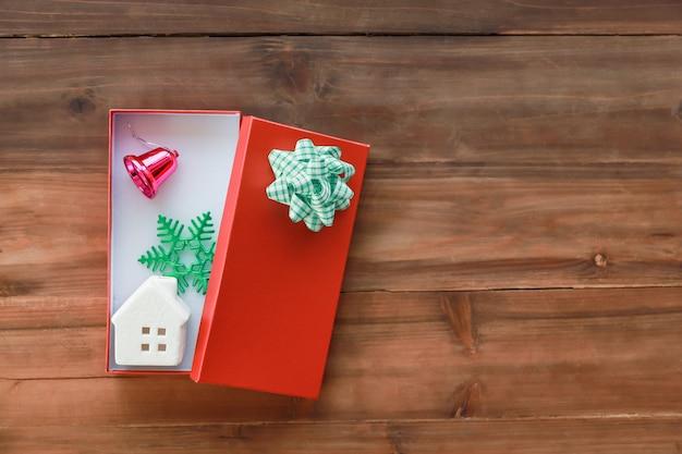 Koncepcja nowego roku, świąt i świąt widok z góry na piękne czerwone pudełko z ceramiczną zabawką i starą drewnianą deską ozdobną
