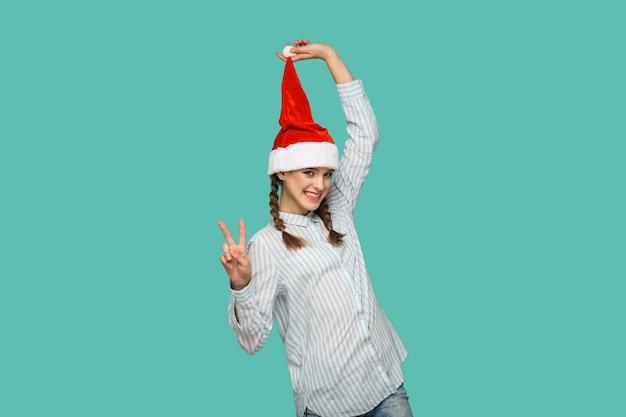 Koncepcja nowego roku. szczęśliwa zabawna piękna dziewczyna w jasnoniebieskiej koszuli w paski, stojąca i trzymająca czerwony świąteczny kapelusz, pokazując znak zwycięstwa lub pokoju patrząc na kamerę. kryty na białym tle na zielonym tle.