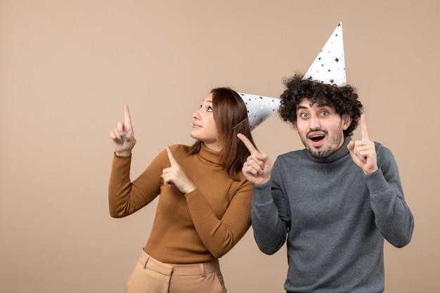 Koncepcja nowego roku z uroczą podekscytowaną szczęśliwą młodą parą nosić nowy rok kapelusz na szarym obrazie