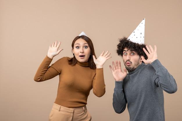 Koncepcja nowego roku z zszokowaną młodą parą nosić kapelusz nowy rok dziewczyna i facet na szaro