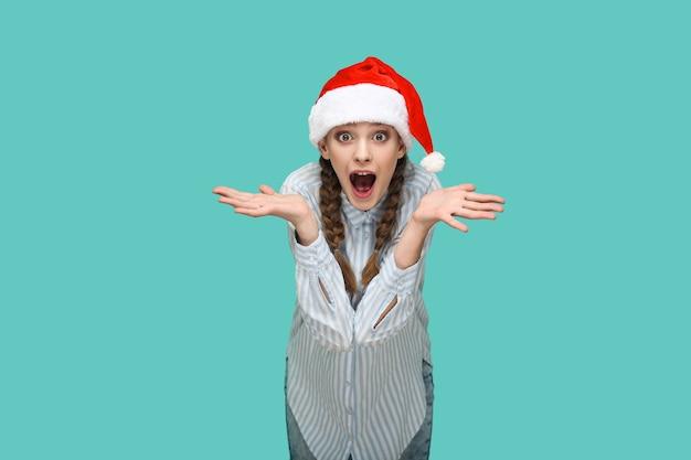 Koncepcja nowego roku. zdumiona piękna dziewczyna w jasnoniebieskiej koszuli w paski w czerwonej czapce świątecznej stoi i patrzy na kamerę z podniesionymi rękami i zdziwioną twarzą. studio strzał na białym tle na zielonym tle.