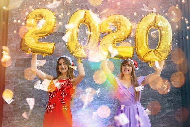 Koncepcja obchodów nowego roku. dwie piękne kobiety ze złotymi balonami 2020