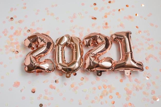 Koncepcja obchodów nowego roku i bożego narodzenia 2021. balony foliowe w postaci cyfr 2021 i konfetti na różowym tle. balony powietrzne. dekoracja świąteczna.