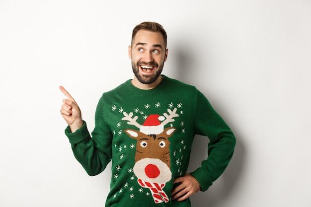 Koncepcja obchodów nowego roku i ferii zimowych. marzycielski brodaty mężczyzna w zielonym świątecznym swetrze, wskazujący na lewy górny róg i uśmiechający się rozbawiony, białe tło.