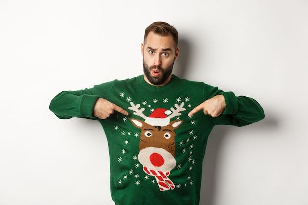 Koncepcja obchodów nowego roku i ferii zimowych. mężczyzna wskazujący na swój śmieszny świąteczny sweter i patrząc zdezorientowany, stojący na białym tle.