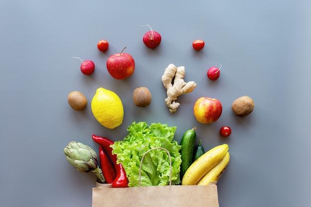 Koncepcja obdzierania zdrowej i ekologicznej żywności. eko torebka z posypanymi liśćmi sałaty, jabłkami, kiwi, rzodkiewką, cytryną, ogórkiem, bananem, karczochami, czerwoną słodką papryką i korzeniem imbiru.