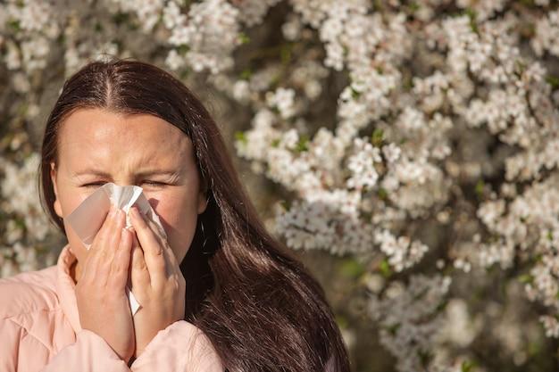 Koncepcja objawów alergii wiosny, młoda kobieta kichanie przed kwitnące drzewo, alergia na pyłki i sezon kwitnienia, opieka zdrowotna
