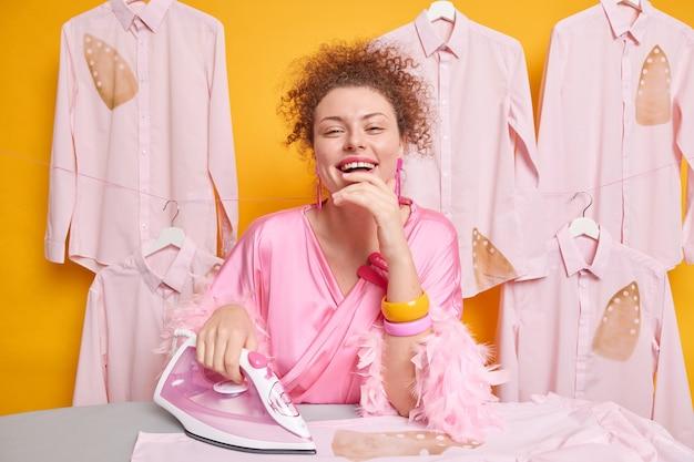 Koncepcja obowiązków domowych. szczęśliwa uśmiechnięta gospodyni domowa żelazka ubrania w domu pozuje w szlafroku w pobliżu deski do prasowania na białym tle nad żółtą ścianą. pozytywna pani domu robi prace domowe