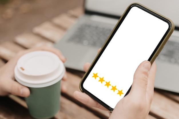Koncepcja obsługi klienta. mężczyzna z5gwiazdkami wswoim telefonie. internetowy system rankingowy.