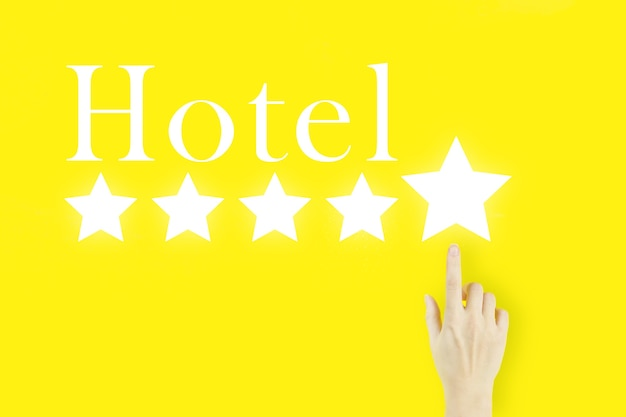 Koncepcja obsługi klienta. młoda kobieta palca wskazującego z hologramem pięć gwiazdek i tekst hotel na żółtym tle.