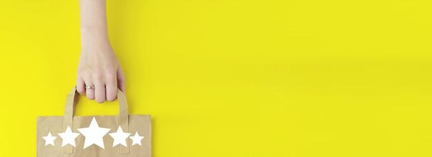 Koncepcja obsługi klienta. torba na zakupy z recyklingu brązowego papieru w ręku z hologramem pięć gwiazdek 5 ocena ikona na żółtym tle, płaskie świeckich. koncepcja sprzedaży letniej. koncepcja usługi dostawy.