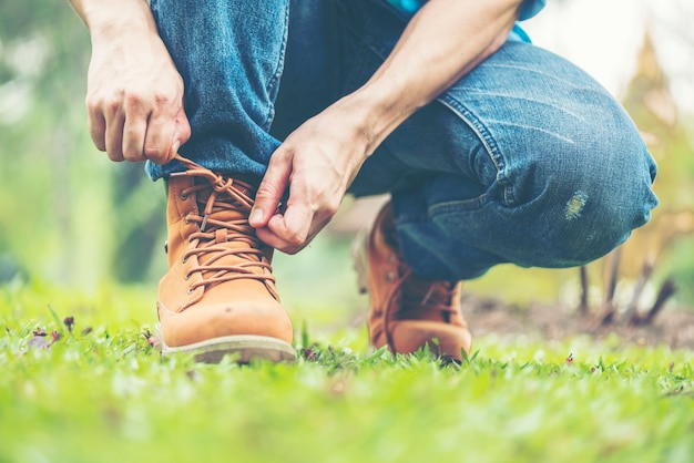 Koncepcja obuwia. przystojny mężczyzna w dżinsach uklęknął, żeby zawiązać sznurowadła