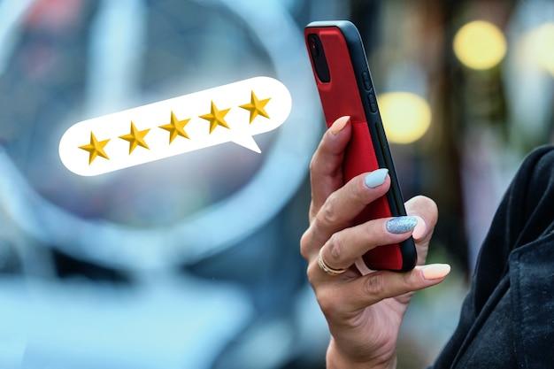 Koncepcja oceny w gwiazdkach. osoba trzyma smartfon i korzysta z internetu.