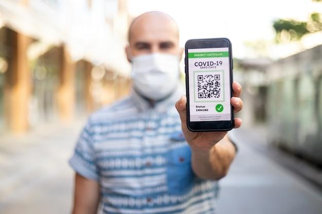 Koncepcja ochrony covid-19. szczęśliwy młody mężczyzna trzymający telefon komórkowy z cyfrowym międzynarodowym paszportem zdrowotnym, potwierdzającym szczepienie, gotowy do podróży