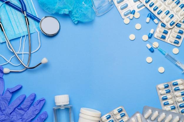 Koncepcja ochrony przed koronawirusem - stetoskop, maska ochronna, tabletki, strzykawka na niebieskim tle.