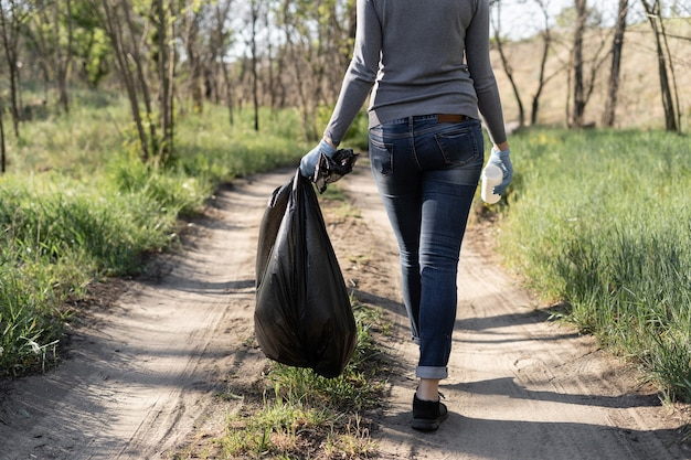 Koncepcja ochrony środowiska. jedna kobieta nosi czarny worek na śmieci. oczyszczono park