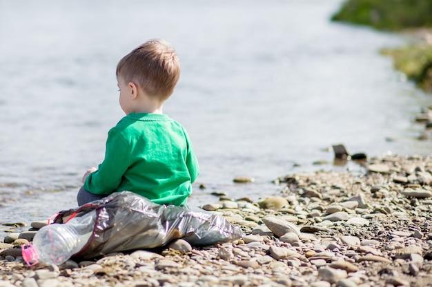 Koncepcja ochrony środowiska - mały chłopiec zbiera śmieci i plastikowe butelki na plaży i wyrzuca je do kosza.