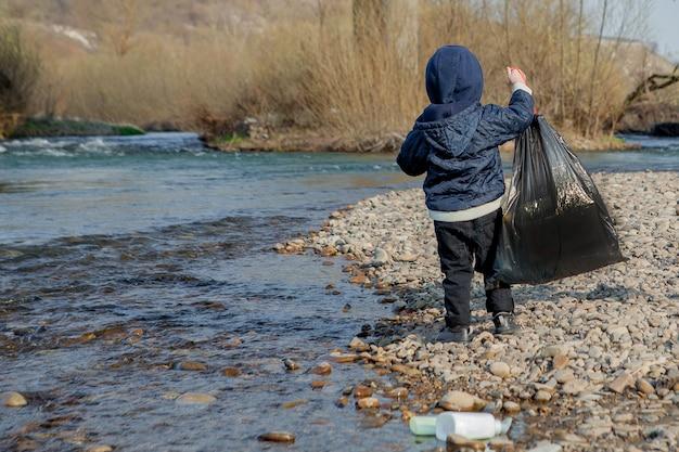 Koncepcja ochrony środowiska, mały chłopiec zbierający śmieci i plastikowe butelki na plaży i wyrzucany do kosza.