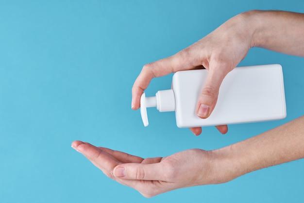 Koncepcja ochrony zdrowia przed epidemią covid-19 z antyseptykiem. kobieta myje ręce za pomocą środka dezynfekującego lub żelu antyseptycznego jako środka zapobiegającego koronawirusowi