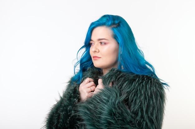 Koncepcja ochrony zwierząt, mody i ludzi - piękna dziewczyna ubrana w sztuczne futro z niebieskimi włosami stojąca na białej ścianie.