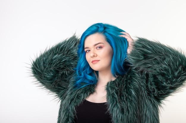 Koncepcja ochrony zwierząt, mody i włosów - piękna dziewczyna ubrana w sztuczne futro z niebieskimi włosami stojąca na białej ścianie.